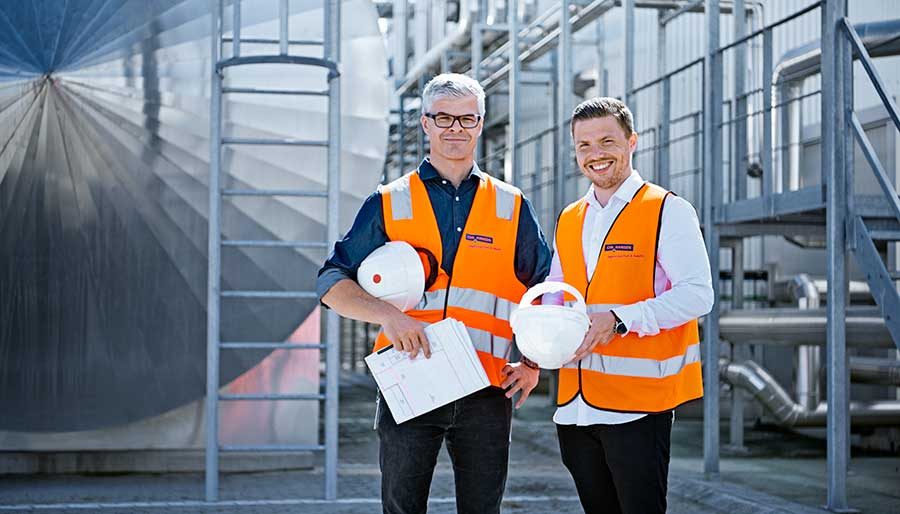 Two men standing at production site