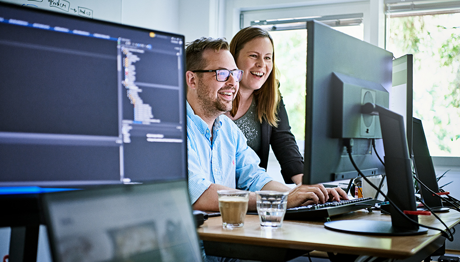 IT employees smiling looking at computer
