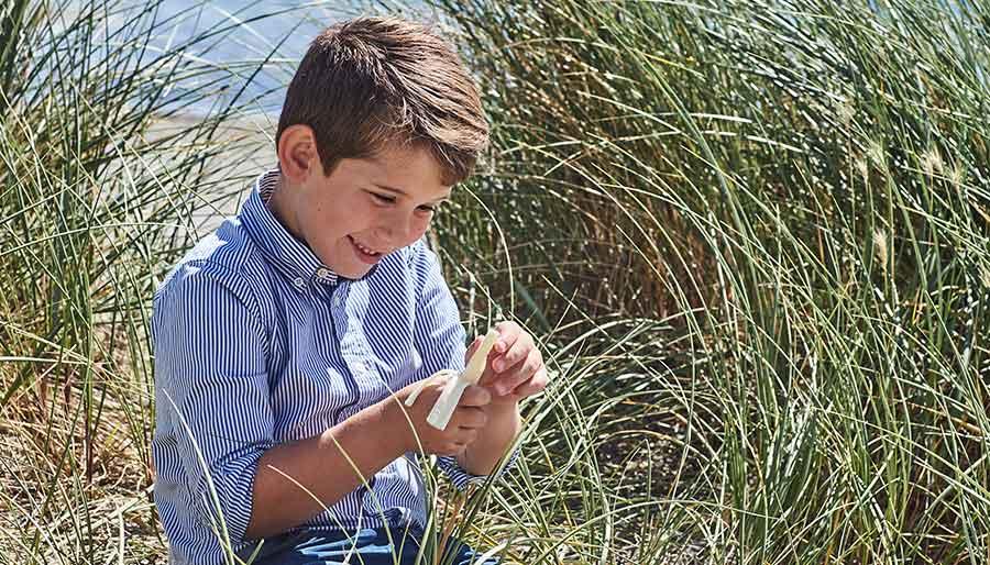 Boy eating cheese on beach