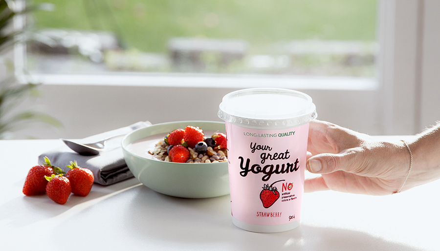 Yogurt in packaging and bowl with strawberries
