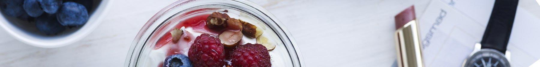 Yogurt with berries next to lipstick and watch