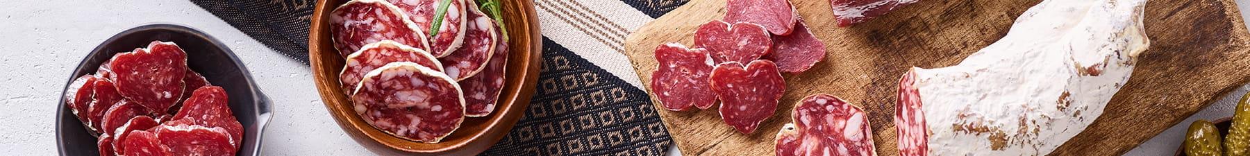 Sliced salami on wooden board